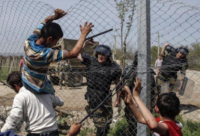 Un policía amenaza a los inmigrantes en Idomeni.