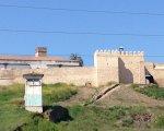 Una foto de la muralla ya restaurada con la casa antigua de la luz.