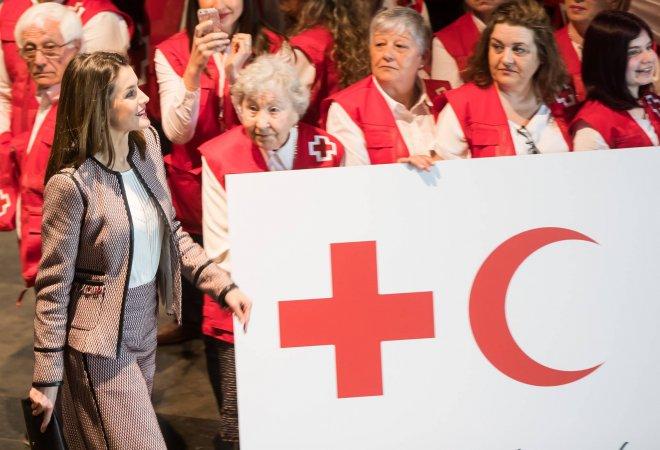 La reina Letizia saluda a su llegada a los voluntarios de la Cruz Roja presentes en el acto del Palacio de Congresos de Santiago.